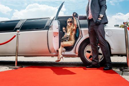 Conductor ayudando a mujer VIP o estrella fuera de limusina en la alfombra roja a una recepción