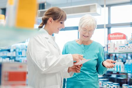Pharmacist servicing senior customer in her pharmacy holding bottle with pills in her hand