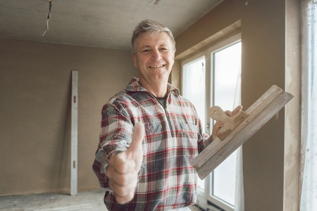 Friendly plasterer giving thumbs-up in the interior of newly constructed house
