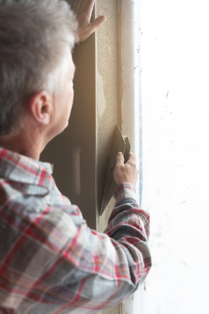 Diligent plasterer working on a window opening