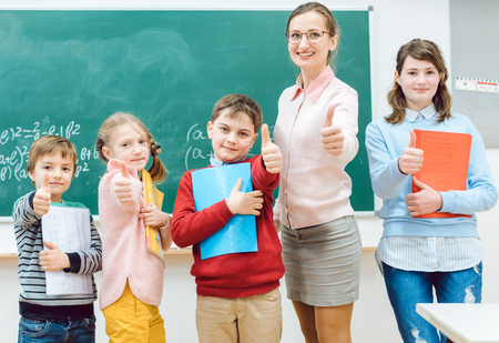 Pupils and teacher showing thumbs-up in school having fun in class Banco de Imagens