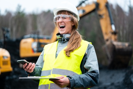Worker woman in open-cast mining using phone talking to manager