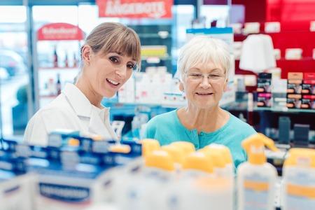 Chemist and customer standing in pharmacy between the shelves talking Reklamní fotografie