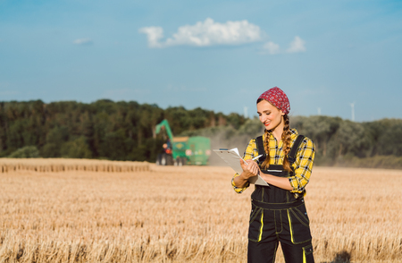 Farmer woman monitoring business progress of the harvest with agricultural machinery in the background