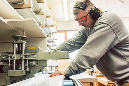 Tinner travaillant sur des tôles dans son atelier à la scie