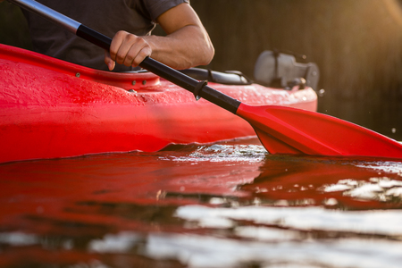 Close-up of a man rowing in red kayak using paddle on lake
