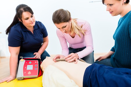 Female attendees of first aid class learning how to use defibrillator
