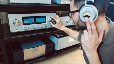 Homme augmentant le volume de la chaîne hi-fi domestique pour une musique plus forte Banque d'images