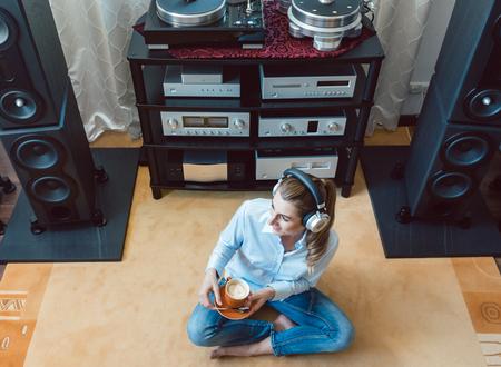 Femme écoutant de la musique à partir d'une chaîne hi-fi à la maison Banque d'images