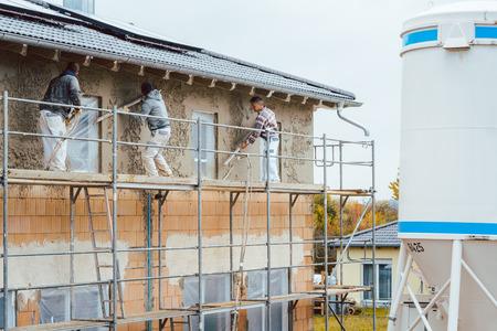 Pleisterwerker op steiger die aan buitenmuur van huis werkt Stockfoto