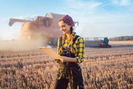 Rolnik na polu podczas żniw ze schowkiem wykonującym kontrolę Zdjęcie Seryjne