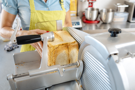 Close-up of a womans hand putting bread in machine