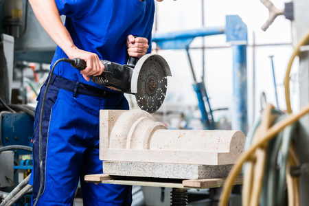Female sculptor cutting stone with angle grinder in workshop Stock Photo