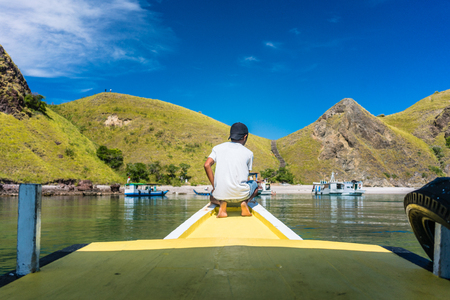 Rear view of a young man enjoying the tranquil view of Padar Island, while sitting on a jetty in a sunny day during summer vacation in Indonesia Stock Photo