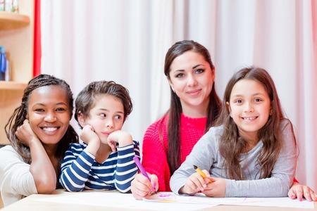 Porträt einer lächelnden Frau, die mit Kindern sitzt und auf dem Tisch zeichnet