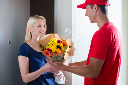 Smiling young female customer receiving beautiful flower bouquet from delivery man