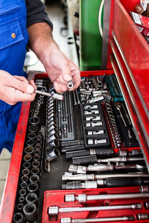 Mechanic man holding tool for repair and diagnostics of cars in the garage