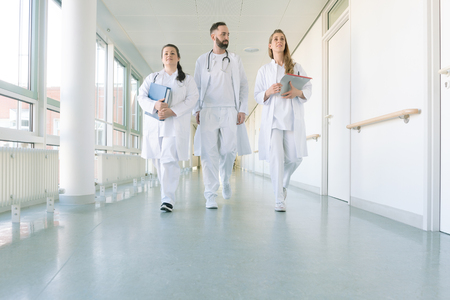 Doctors, two women and a man, in hospital walking down the corridor