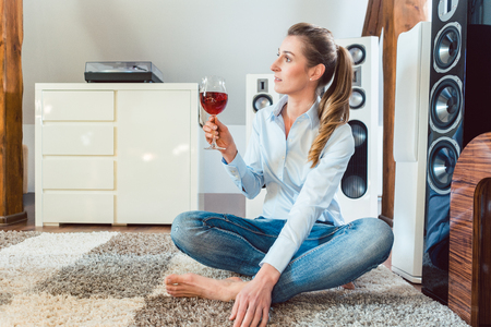 Woman having glass of wine in front of Hi-Fi speakers enjoying the drink and the music