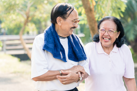 Close-up of happy senior couple walking together in the park