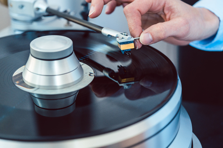 Woman putting needle on vinyl to play a record on turntable Stock Photo