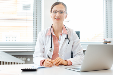 Beautiful doctor with computer in her surgery or office looking into the camera
