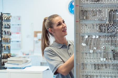 Women key maker in her shop looking for blanks