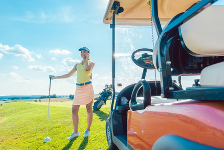 Full length of an active and cheerful woman, wearing modern golf apparel while talking on mobile phone on the golf course near the cart in a sunny day of summer Banco de Imagens
