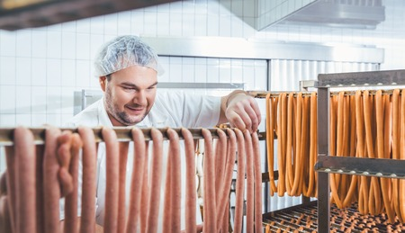 Butcher man making sausages ready to be smoked putting them on rack Stok Fotoğraf