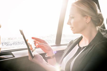 Businesswoman sitting in sunlight inside the car using digital tablet