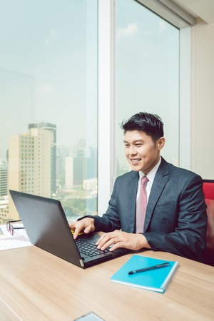 Smiling businessman using laptop in the office