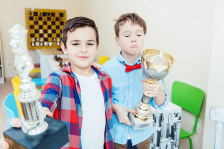 Two boys having won a chess tournament holding trophy up in the air Standard-Bild