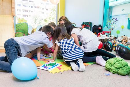 Gruppe von Vorschulkindern, die ihren erfahrenen Lehrer während einer pädagogischen Aktivität im Klassenzimmer eines modernen Kindergartens umgeben surrounding Standard-Bild