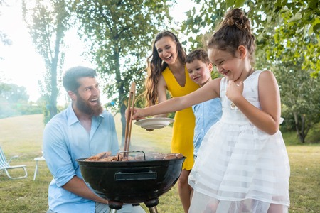 Cute funny girl using wooden tongs while preparing meat on the BBQ charcoal grill in front of her father, mother and brother during picnic in summer