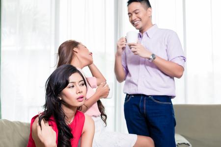 Nahaufnahme einer Frau, die auf ihre Freunde achtet, die eine Kaffeetasse halten und miteinander reden