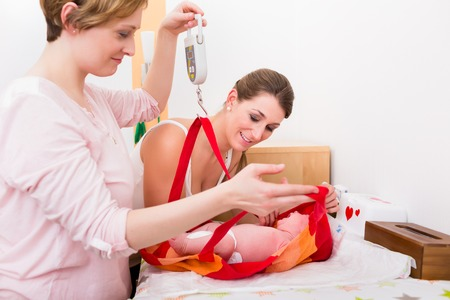 Close-up of two woman looking at baby in the weighing bag