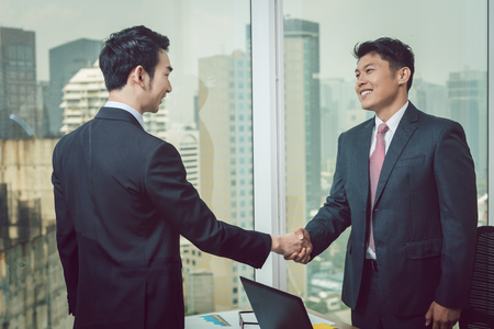 Smiling young businessman shaking hand with his partner standing near the window