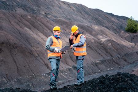 Los trabajadores de pie en el pozo de operación minera a cielo abierto