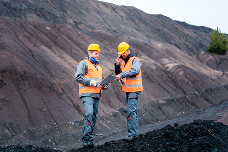 Workers standing in open-cast mining operation pit