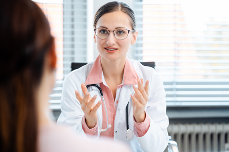 Young female doctor seeing woman patient in consultation