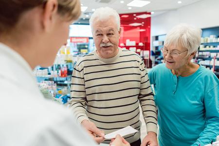 Pharmacist getting prescription slip from senior couple in her pharmacy