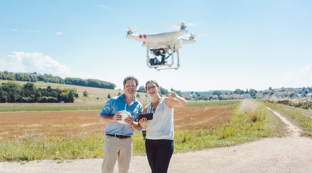 Crew or man and woman operating a drone to utilize it for a photo or film shoot Imagens