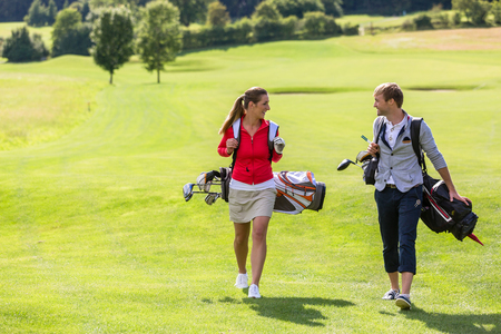 Fit young couple carrying golf bag while walking on golf course Stock Photo