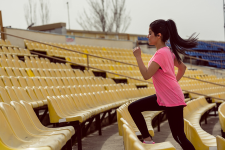 Side view of a woman running on stadium staircase