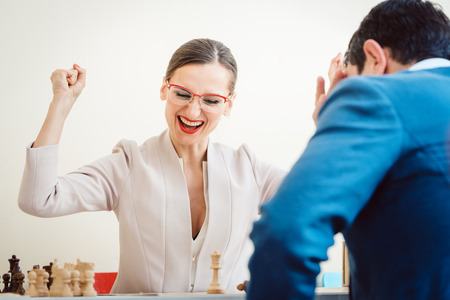 Excited businesswoman winning in chess due to better strategy