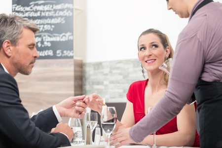 Man holding his wifes hand in front of waitress at restaurant