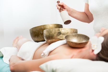 Therapist giving sound therapy to woman with singing bowl in spa Фото со стока