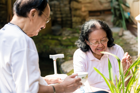 Senior man bringing coffee for his wife taking care of plants