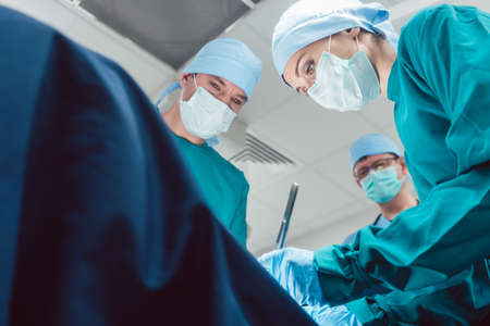 Team of surgeons in operation room during surgery from low angle view Foto de archivo