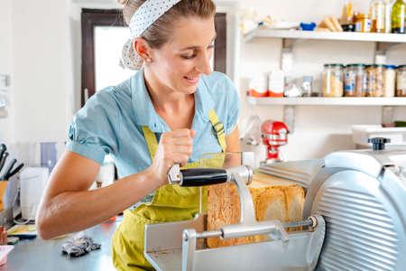 Happy woman putting bread in machine in kitchen